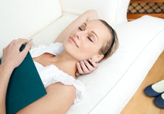 Tired woman sleeping while reading a book. At home Stock Photo