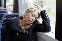 Tired woman sleeping while riding to work in public transport Stock Photos