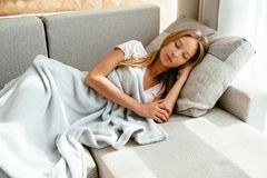 Tired woman sleeping on sofa in living room at home. Royalty Free Stock Image