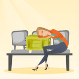 Tired woman sleeping on suitcase at the airport. Royalty Free Stock Images