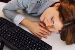 Tired woman sleeping at work. Holding her head on the desk Stock Image