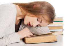 Tired woman slepping on books.  Royalty Free Stock Photography