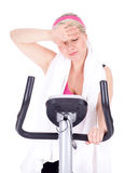 Tired woman on stationary bicycle Stock Image