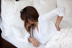 Tired woman suffering from back pain having bad sleep. Tired young woman waking up in white bedroom feeling back pain, exhausted female suffering from sudden royalty free stock photo