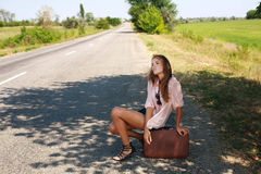 Tired woman in with suitcase hitchhiking on road in country Stock Images