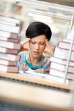 Tired woman surrounded with books. Tired woman with headache sitting at the desk surrounded with piles of books Royalty Free Stock Photography