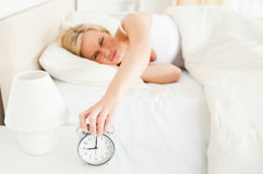 Tired woman switching off her alarm clock Royalty Free Stock Image