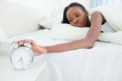 Tired woman switching off her alarm clock Stock Photos