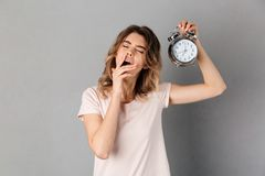 Tired woman in t-shirt yawns and holding alarm clock. With closed eyes over grey background Stock Image