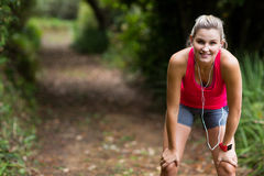 Tired woman taking a break while jogging Royalty Free Stock Photo