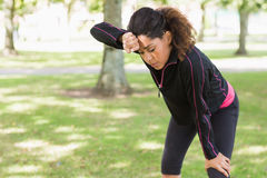 Tired woman taking a break while jogging in park Royalty Free Stock Photo