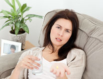 Tired woman taking her medicine lying on the sofa Royalty Free Stock Photo
