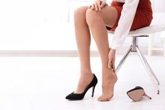 Tired woman taking off shoes at office stock photos