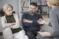 Tired woman talking to mediator. Tired women talking to a mediator about her bad relationships with her husband, who is quarrelsome Royalty Free Stock Images