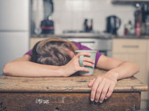 Tired woman with tea in kitchen. A tired young woman is having a cup of tea and is resting her head on a table Royalty Free Stock Photos