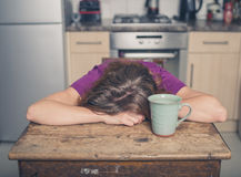 Tired woman with tea in kitchen stock photos