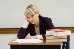 Tired Woman Teacher. Woman teacher or instructor in a college, university, high school, middle school, elementary classroom tired and weary of grading papers and Stock Photo