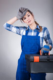 Tired woman with a toolbox Stock Images