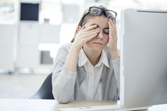 Tired woman touching her eyes Royalty Free Stock Photo