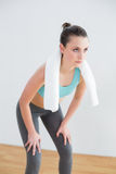 Tired woman with towel around neck at fitness studio stock images