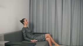 Tired woman with TV remote control sitting on the couch and turning on the TV.  stock video footage