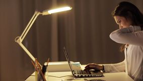 Tired woman typing on laptop at night office. Business, overwork, deadline and people concept - tired woman typing on laptop at night office stock video footage