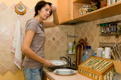 Tired woman washes tableware Stock Images