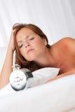 Tired woman watching alarm clock Stock Photos