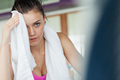 Tired woman wiping face while working on row machine Stock Image