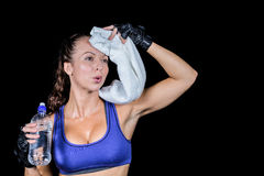Tired woman wiping sweat while holding water bottle. Against black background Royalty Free Stock Photo