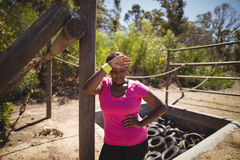 Tired woman wiping sweat after workout during obstacle course Stock Photography