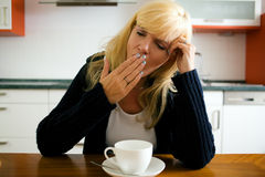 Tired woman yawning. In front of a mug full with coffee Stock Image