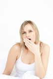 Tired woman yawning sitting on her bed Royalty Free Stock Photo