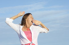 Tired woman yawning sky background Stock Images