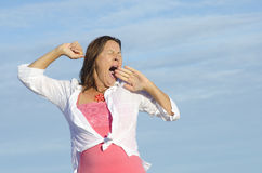 Tired woman yawning sky background Royalty Free Stock Image