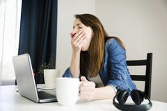Tired woman yawning while working on laptop at desk. In natural light Royalty Free Stock Photos