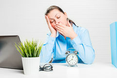 Tired woman yawns and wants to sleep at work. In the office Royalty Free Stock Photography