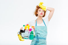 Tired woman in yellow gloves holding box with detergents. Tired attractive young woman in yellow gloves and blue apron standing and holding box with detergents Stock Photos