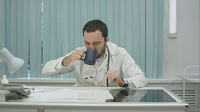 Tired  from work, bearded doctor drink from cup and continue woking with documents and x-rays. Tired  from work, bearded male doctor drink from cup and continue Stock Image
