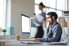 Tired of work. Tired or bored young businessman watching video conference and covering his mouth by hand in office Royalty Free Stock Images
