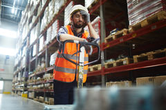 Tired of work. Tired worker with forklift touching his forehead Royalty Free Stock Photo