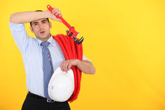 Tired worker. Wiping his forehead Royalty Free Stock Image