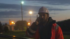 Tired worker in hard helmet talking by phone at hignt. 4k shot stock video