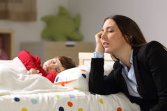 Tired worker mother sleeping beside her daughter. Tired worker mother wearing suit sleeping beside her sleepy daughter on a bed at home Royalty Free Stock Photos