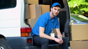 Tired worker of moving company resting, sitting in van full of cardboard boxes stock photography