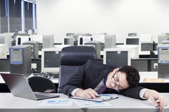 Tired worker napping at workplace. Caucasian entrepreneur sleeping on the table with laptop and financial chart. Shot in the workplace Stock Photo