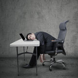 Tired worker sleeping on laptop at desk Royalty Free Stock Image