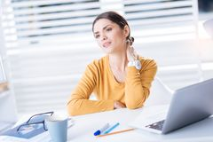 Tired worker touching the aching neck and wishing to go home. Neck pain. Exhausted qualified worker feeling unwell and touching the neck while having a sudden Stock Photos