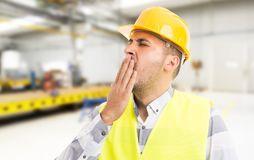 Tired workman yawning sleepy on workplace inside factory royalty free stock photos