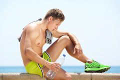Tired workout man sitting by the sea with bottle of water Royalty Free Stock Images